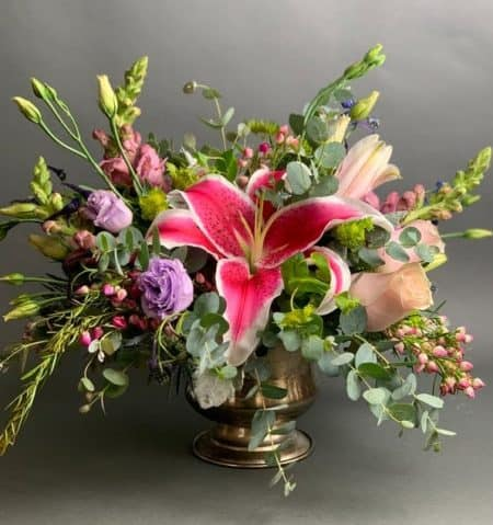 Lush, romantic, bold, beautiful. This all around design is perfect for any occasion or location. A mix of vibrant and soft pinks and purples with stylish greenery in an attractive compote vase.